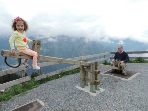 Moore teeter-totters with his daughter in the Alps.