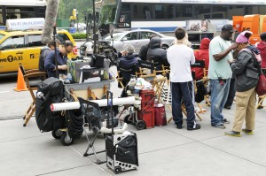 "On the Manhattan set of the film ""Arbitrage"" in May 2011. A sound technician (left) checks his equipment while several other crew members check out a take on small monitors (right)."