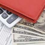 Money in Wallet and calculator on tax form background