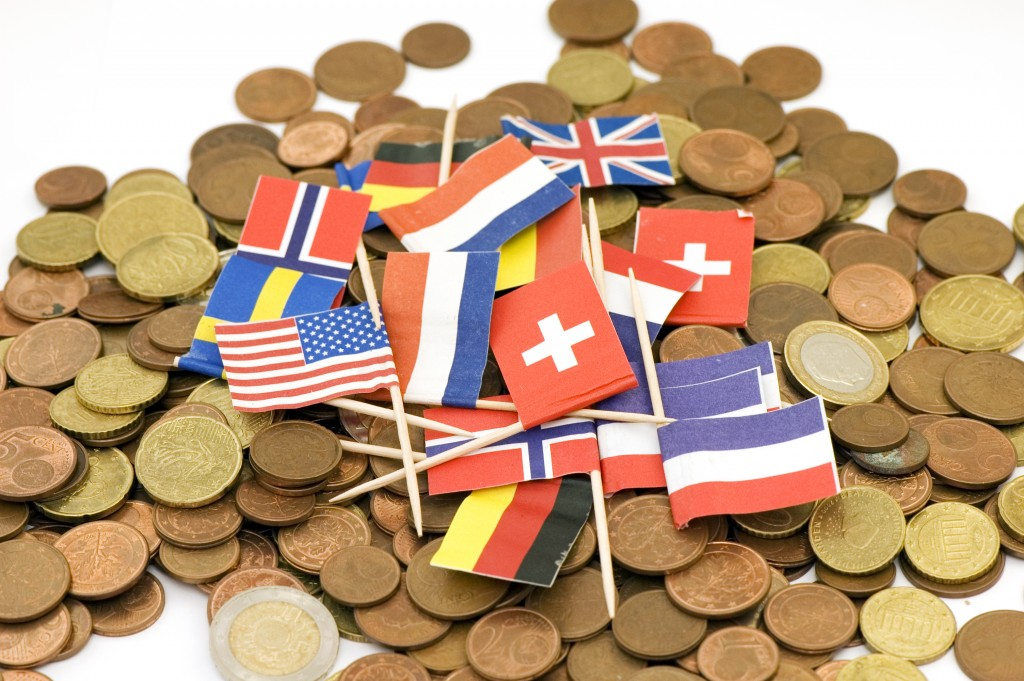 Close-up of international flags sitting on euro coins background.