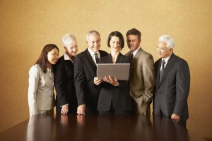 Group of businesspeople standing with laptop behind table