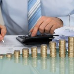 Close-up Of Businessman Calculating Bills In Front Of Stacked Coins