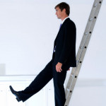 Side profile of a businessman moving down a ladder