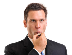 Businessman blowing whistle on white
