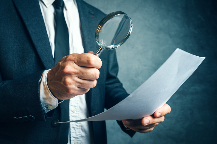 Tax inspector investigating financial documents through magnifyi