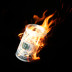 Burning one hundred dollar bills rolled