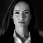 Business woman in suit outfit close up portrait, in front of a blurry background