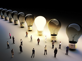Light bulbs in a row with one being on, large group of people with a few moving to the light.